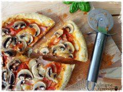 Kawałek pizzy capriciosa z sosem pomidorowym i pieczarkami