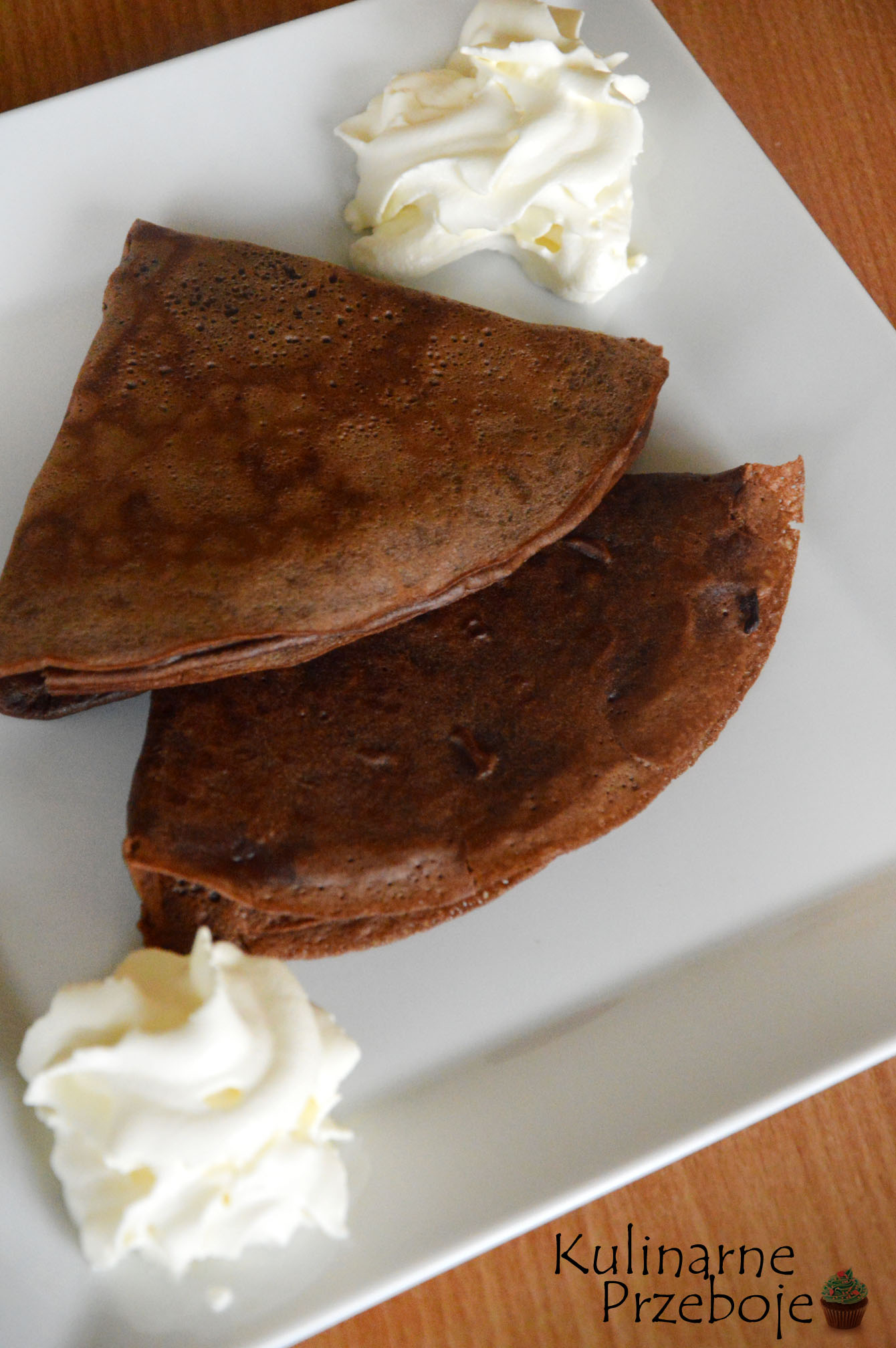 Dwa naleśniki czekoladowe na białym talerzu z dodatkiem bitej śmietany
