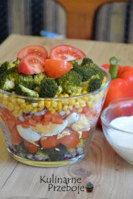 Piękna kolorowa sałatka warstwowa z jajkiem, brokułem, kukurydzą konserwową i czerwoną papryką