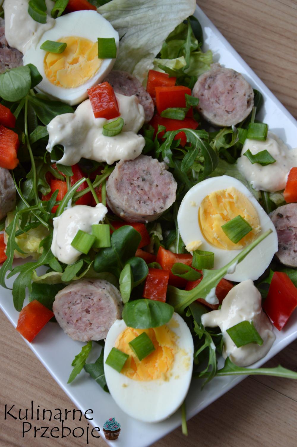 Kolorowa sałatka na talerzu z jajkiem, białą kiełbasą i szczypiorkiem